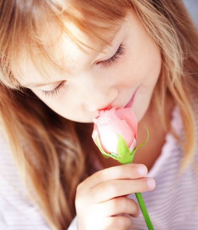 Cute little girl smelling rose photo
