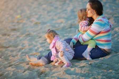Mother resting at beach with her daughters photo