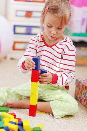 Child playing with blocks in the kindergarten photo
