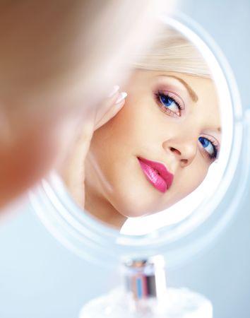 spiegels: Jonge vrouw op zoek in cosmetische spiegel