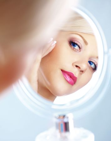 reflection in mirror: Young woman looking in cosmetic mirror