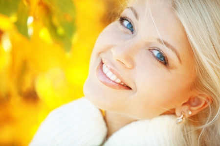 perfect smile: Portrait of beautiful young woman walking outdoors in autumn