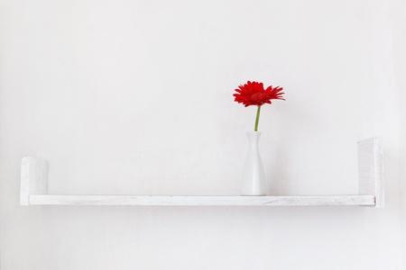 estanterias: Estante decorativo en la pared blanca con flor vaso de ina en �l