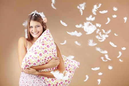 bedclothes: Beautiful teenage girl holding a pillow studio shot Stock Photo