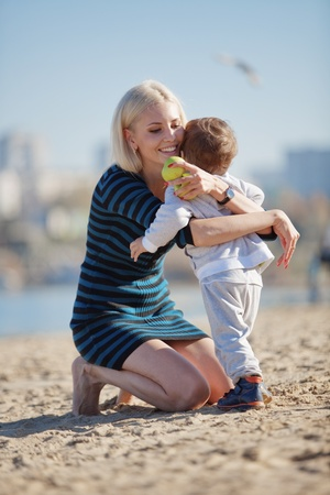 Young mother with her kid resting at the beach photo