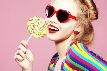 paletas de caramelo: Chica glamour vistiendo el coraz�n en forma de gafas de sol celebraci�n lollipop Foto de archivo