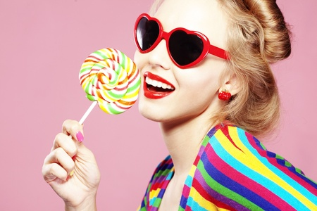 Glamourous girl wearing heart shaped sunglasses holding lollipop Stock Photo