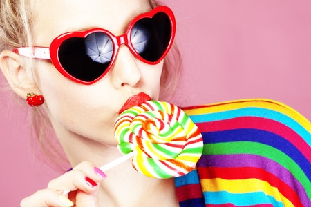 Glamourous girl wearing heart shaped sunglasses holding lollipop Stock Photo - 8354451