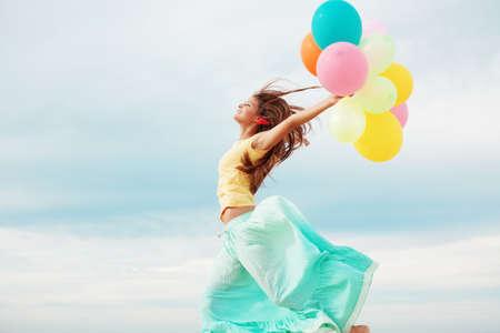 dynamic movement: Feliz manojo de explotaci�n de chica de aire colorido globos en la playa