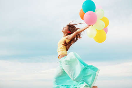 dynamic motion: Happy girl holding bunch of colorful air balloons at the beach