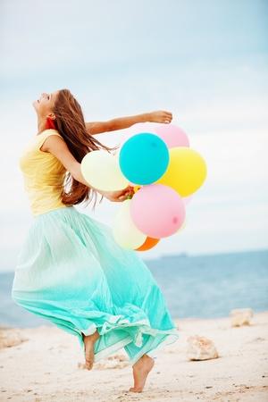 Feliz manojo de explotaci�n de chica de aire colorido globos en la playa Foto de archivo - 8787515