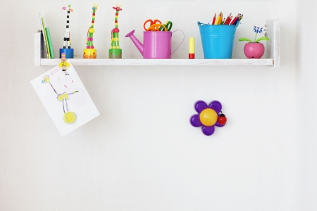Kids shelf on white wall with toys on it Stock Photo
