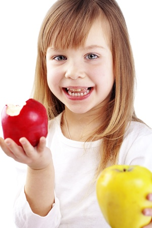 over eating: Cute kid girl eating apples over white
