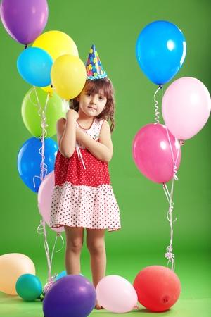 Child celebrating birthday on green studio background photo