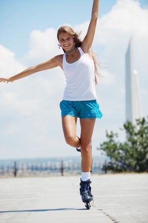 Beautiful teenage girl rollerskating in park photo