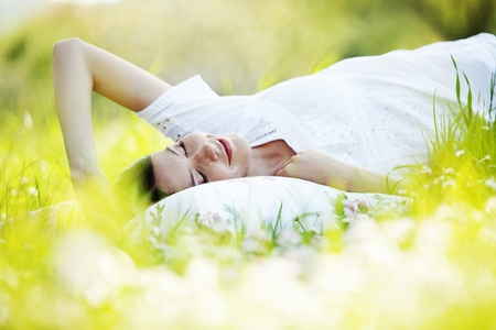 lay: Young cute girl resting on soft pillow in fresh spring grass