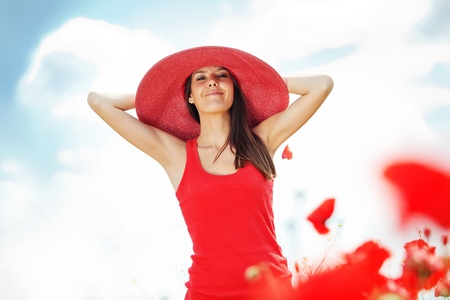 spring hat: Portrait of young beautiful woman at poppy field