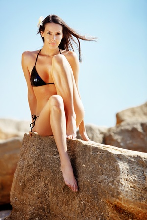hot girl legs: Closeup portrait of beautiful young woman with golden tan resting at beach in summer
