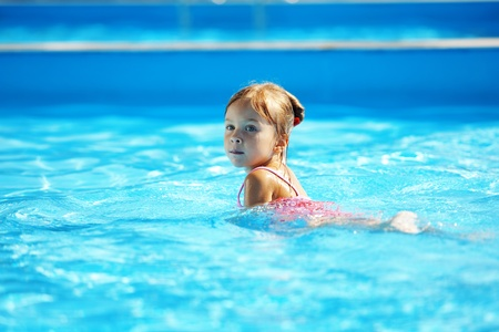 Little girl having fun in swimming pool Stock Photo