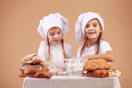 preparing dough: Little cute bakers studio shot