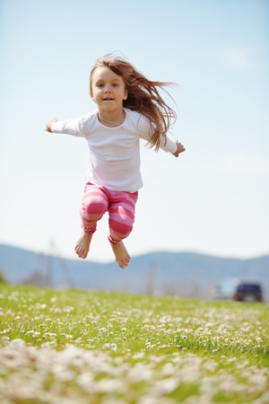 Kid girl jumping on the grass at spring photo