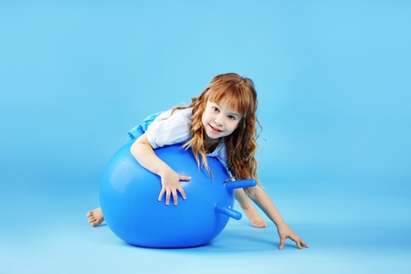 Child with gymnastic ball on bleu studio background Stock Photo - 9824771