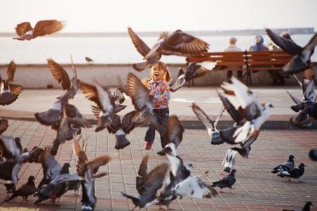 pigeons: Enfant jouant avec colombes dans la rue de la ville
