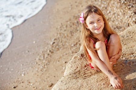 Cute child wearing swimsuit resting at beach in summer photo