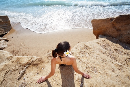 Closeup portrait of beautiful young woman with golden tan resting at beach in summer photo
