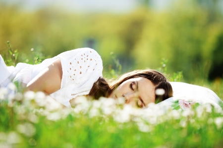 Young cute girl resting on soft pillow in fresh spring grass photo