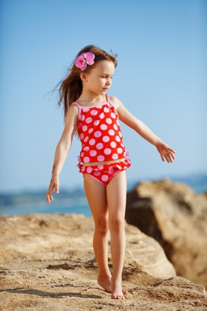 Cute child wearing swimsuit walking at beach in summer Stock Photo - 9842899