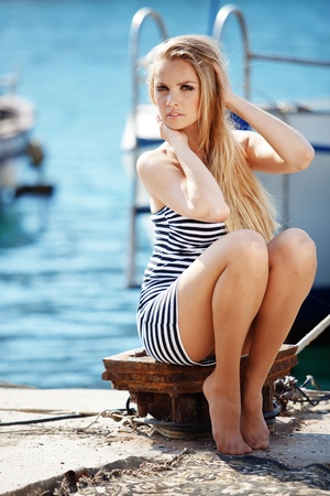 Beautiful sexy woman wearing sailor striped dress posing at beach