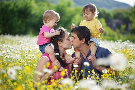 Gelukkig jong gezin met een tweeling rusten buiten Stockfoto