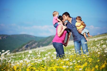 descansando: Familia joven feliz con gemelos de descanso al aire libre