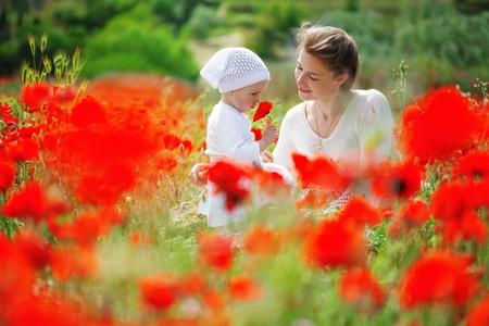 poppy field: Moeder spelen met haar peuter kind in papaver veld Stockfoto