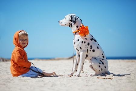 walking alone: Ni�o caminando sola con su perro en la playa hermosa