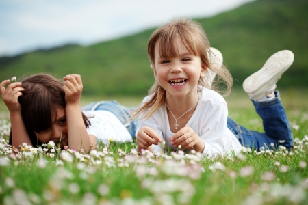 child: Cute happy children playing in spring filed