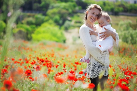 Mother playing with her toddler child in poppy field photo