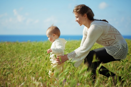 toddler walking: Mother walking with her baby in spring green field