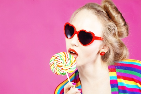 lollipops: Glamourous girl wearing heart shaped sunglasses holding lollipop Stock Photo