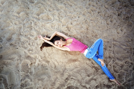 Portrait of very pretty beautiful girl lying on sand photo