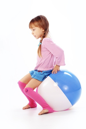 Child with colorful ball on white studio background Stock Photo