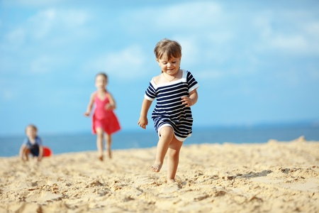 Kids playing running on sand at the beach photo