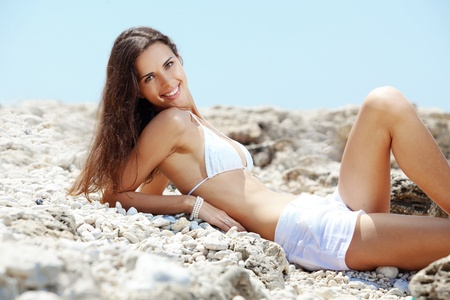hot body girl: Portrait of beautiful young woman with golden tan resting at beach in summer