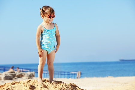 Happy child playing at the beach in summer photo