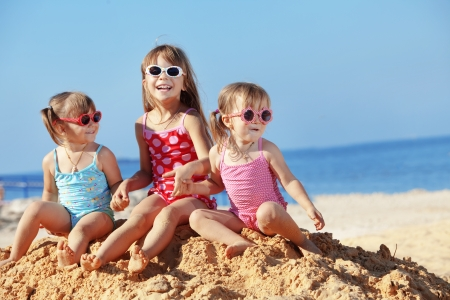 Happy kids playing at the beach in summer photo