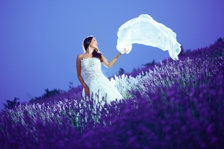 wedding portrait: Bride posing with flying veil at lavender field at night
