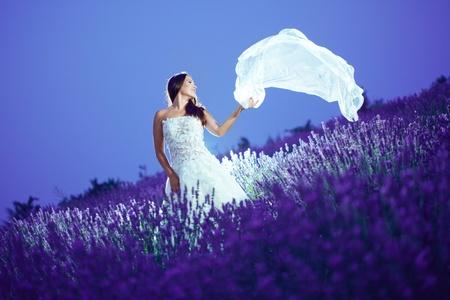 wedding night: Bride posing with flying veil at lavender field at night