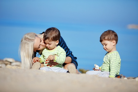 Young mother with her infant kids resting at the beach photo