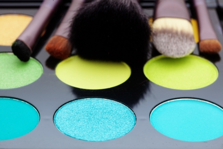 eyeshadows: Make-up colorful eyeshadow palette with makeup brushes on it Stock Photo